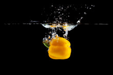Yellow Pepper Falling Into Water And Splashing Against Black Background