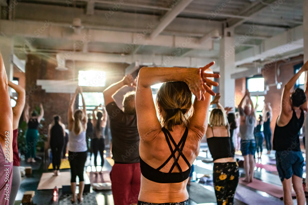 Fototapety, obrazy: Diverse group of people in yoga class. A toned lady is seen from behind as she works through a grueling set of yogic moves in a workshop dedicated to sun salutes. With blurry people in background.