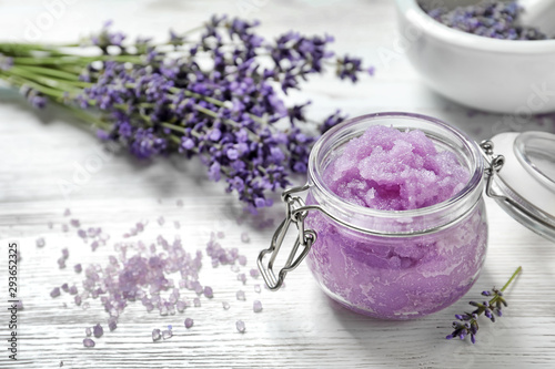 Natural sugar scrub and lavender flowers on white wooden table, space for text. Cosmetic product