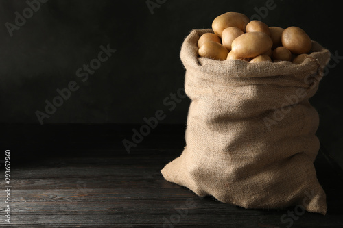 Obraz Raw fresh organic potatoes on wooden table against dark background. Space for text - fototapety do salonu