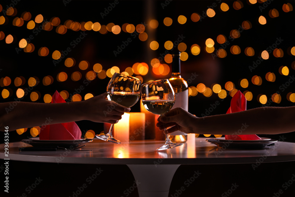 Fototapeta Young couple with glasses of wine having romantic candlelight dinner at table, closeup