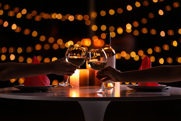 Young couple with glasses of wine having romantic candlelight dinner at table, closeup