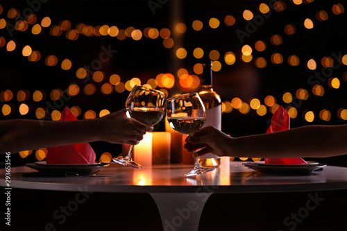 Fototapeta Young couple with glasses of wine having romantic candlelight dinner at table, closeup obraz
