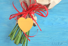 Stems Of Roses In Craft Paper With A Red Bow And Yellow Paper Heart For Greeting Text On Blue Background. Love Letter And Flower Delivery Service On Valentines Day. Present For Mother's Day.
