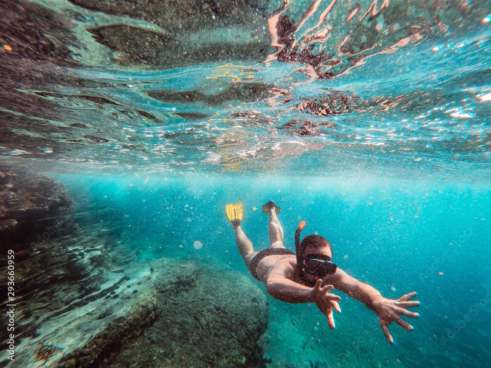 Fototapeta Underwater photo of men diver snorkeling in the sea
