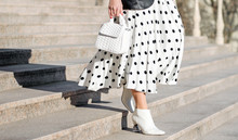Fashionable Bag Close-up In Female Hands.Girl Walks In The City Outdoors. Stylish Modern And Feminine Image, Style. A Woman In A White Dress In Black Peas With A White Bag And White Shoes, Or Shoes.