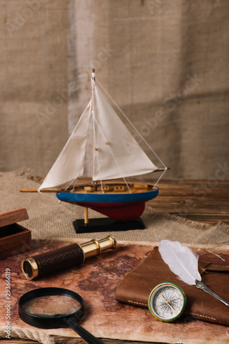 miniature ship, telescope, magnifying glass, leather copy book, compass and nib on old world map and hessian