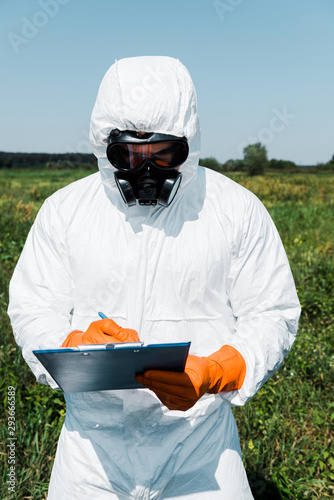 exterminator in protective mask and uniform writing while holding clipboard