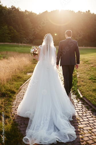 Valokuvatapetti Full length body portrait of young bride and groom walking on green grass of golf course at sunset, back view