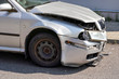 Silver car with its front crashed, plates dented and broken on asphalt road, detail to damaged part
