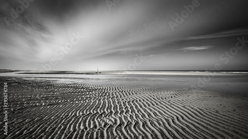 Wall Murals Pale violet Horizontal greyscale shot of mudflat under the crazy cloudy sky