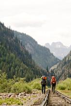 Two People Hiking Along Railro...