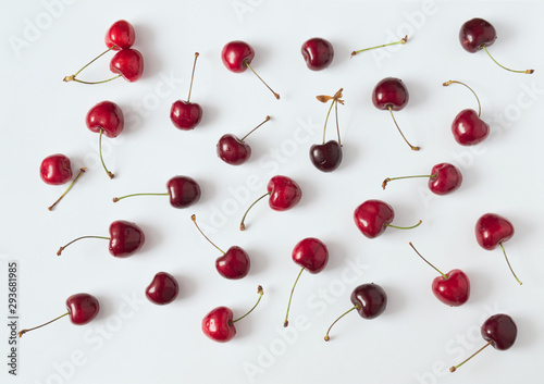 Leinwand Poster composition with red cherries scattered on white paper