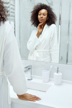 Skin Care. Woman Touching Face, Looking At Mirror At Bathroom