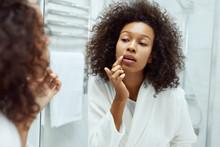 Lips Skin Care. Woman Applying...