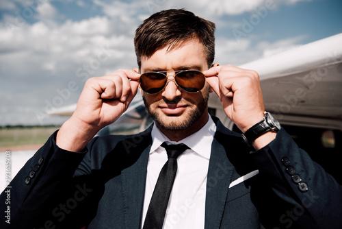confident businessman in formal wear standing near plane