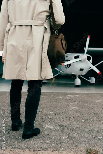 partial view of stylish businessman in coat standing near plane
