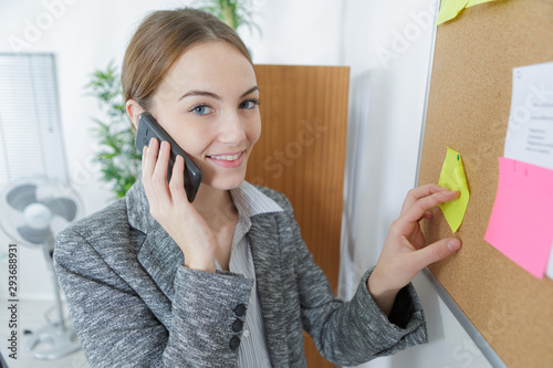 Photo woman on telephone putting post-it note on to board