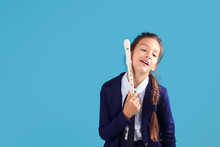 Exhausted, Tired Student Girl Of Music Class Learning To Play On Flute, Blue Background, Copy Space