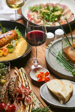 Beautifully Decorated Meals And Glasses Of White And Red Wine On The Wooden Table