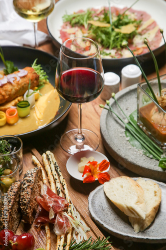 Beautifully decorated meals and glasses of white and red wine on the wooden tabl Fototapet