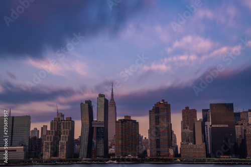 Midtown Manhattan skyline viewed from Long Island City, featuring dramatic sky over the city at sunrise