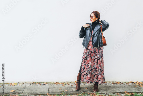 Smiling female dressed boho fashion style colorful long dress with black leather biker jacket with brown leather flap bag posing on the white wall background Wallpaper Mural