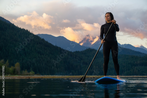 Adventurous Girl on a Paddle Board is paddling in a calm lake with mountains in the background during a colorful summer sunset Canvas Print