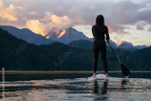 Fond de hotte en verre imprimé Taupe Adventurous Girl on a Paddle Board is paddling in a calm lake with mountains in the background during a colorful summer sunset. Taken in Stave Lake near Vancouver, BC, Canada.