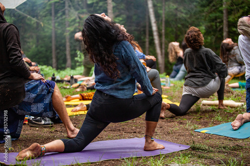 Fotografie, Tablou Diverse people enjoy spiritual gathering A closeup view of a woman wearing denim leggings and shirt with black hair, deep in concentration during a yogic session in a sacred forest clearing
