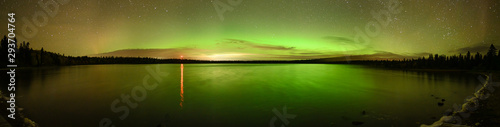 Photo Bright green and orange Aurora (Northern Lights) , stars and clouds reflecting in a calm lake