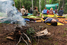 Diverse People Enjoy Spiritual Gathering A Close Up View On A Smoldering Camp Fire As Blurry People Are Seen In Deep Meditation And Prayer In The Background During A Mindful Forest Retreat.