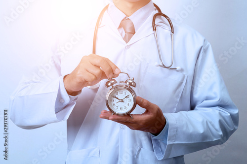 Obraz Doctor holding a clock,  Concept for timing, medical and healthcare - fototapety do salonu