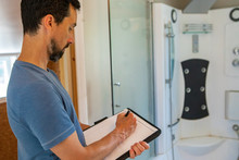 Indoor Damp & Air Quality (IAQ) Testing. A Professional Male Is Seen Close Up And From The Side, Using A Pen & Paper To Take Notes During And Indoor Environmental Quality Assessment Inside A Bathroom.