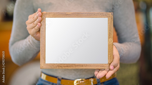 Photo woman holding blank wooden frame in coffee shop