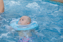 Cute Little Baby With Inflatable Neck Ring In Swimming Pool