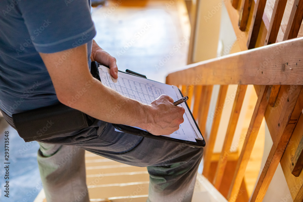 Fototapeta Indoor damp & air quality (IAQ) testing. A close up view on the hand and arm of a building inspector filling in a form, standing on a staircase checking for home defects and environmental qualities.