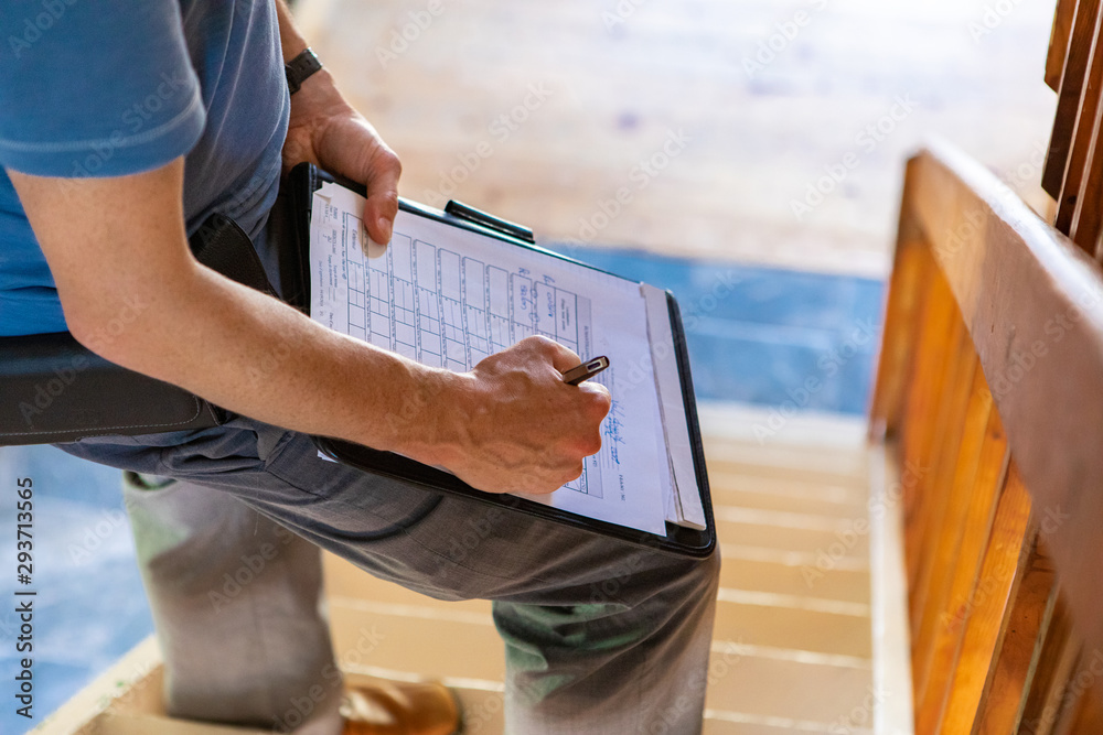 Fototapeta Indoor damp & air quality (IAQ) testing. A close up and high angle view of a professional male wearing blue t-shirt, writing out forms during a home inspection, standing on stairs with copy-space.