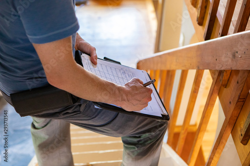 Fototapety, obrazy: Indoor damp & air quality (IAQ) testing. A close up view on the hand and arm of a building inspector filling in a form, standing on a staircase checking for home defects and environmental qualities.