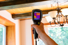 Indoor Damp & Air Quality (IAQ) Testing. A Handheld IR Thermovision Camera Is Seen Closeup, Checking The Insulation Levels Inside A Domestic Home With Blurred Timber Beams In Background.