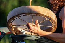 Sacred Drums During Spiritual Singing. A Close Up View On The Hands Of A Drummer Playing A Traditional Handcrafted Native Drum On A Sunny Day In A Public Park As People Celebrate Culture.