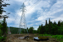 Electricity Pylons In Natural Landscape. A Low Angle View Of Tall Transmission Towers Supporting Overhead Power Lines In A Dense Forest, Man Made Clearing For Industrial Structures With Copy Space.