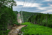 Electricity Pylons In Natural Landscape. Overhead Electricity Lines Are Seen In A Rural Lush Green Landscape With Trees And Vegetation, Juxtaposition Of Industrial Structures & Nature With Copy Space.