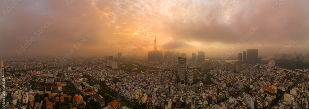 Fototapeta Beautiful aerial urban sunrise in Southeast Asia due to an extreme air pollution level. Ho Chi Minh City, Vietnam has a population of ten million and a manufacturing sector with strong economic growth