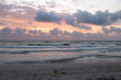 Dawn on the Mediterranean coast, Tunisia Sand in the foreground, small waves, the sun above the horizon, long clouds