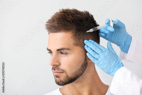 Man with hair loss problem receiving injection on grey background Wallpaper Mural