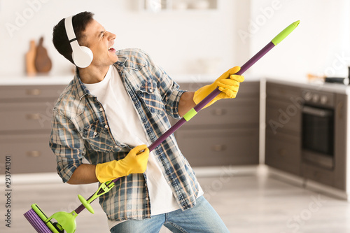 Young man listening to music and singing while cleaning kitchen Wallpaper Mural