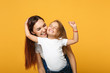 canvas print picture - Woman in light clothes have fun with cute child baby girl 4-5 years old. Mommy little kid daughter isolated on yellow background studio portrait. Mother's Day love family parenthood childhood concept.