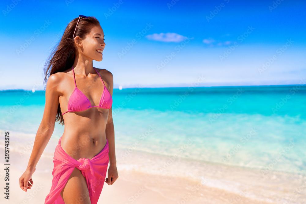 Fototapety, obrazy: Fashion swimsuit bikini woman in hot pink swimwear walking on luxury travel vacation beach destination. Asian model relaxing.