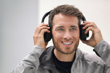 Music Headphones Man Listening To Audiobook Online Or Songs On Phone App. Happy Smiling Young Person Wearing Wireless Earphones. Young Adult Buying Techonology Wearable Device At Store.